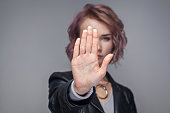 Stop. Portrait of serious beautiful girl with short hairstyle in casual style black leather jacket standing in stop gesture and looking at camera.