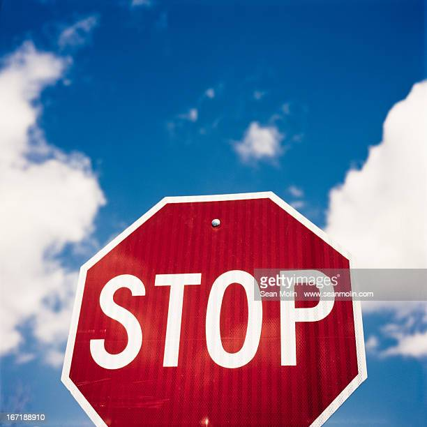 Stop sign against blue sky and puffy white clouds
