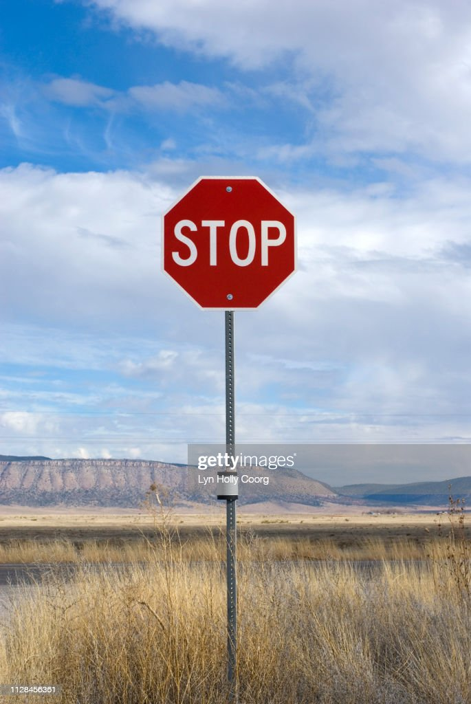 Stop sign by roadside with mountain range in background : Stock Photo