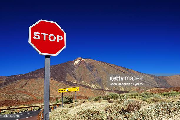 Stop Sign By Rocky Mountain At El Teide National Park Against Clear Blue Sky