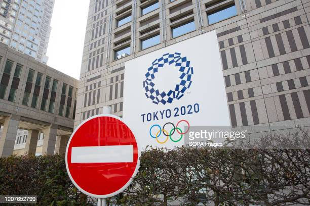 Stop sign in front of the Tokyo Metropolitan Government Building while the Tokyo 2020 Olympic Games banner is seen in the background. Japanese start...