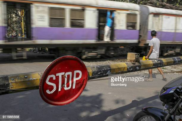 A stop sign is displayed on the barrier of a railway crossing as a train travels past near Chunabhatti railway station in Mumbai India on Saturday...