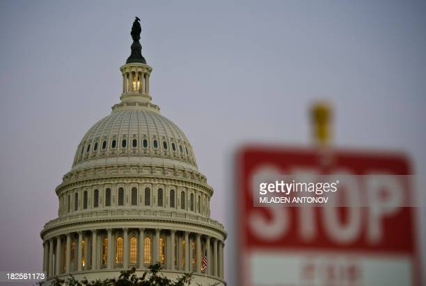 A stop sign is seen at dusk next to the US Congress building on the eve of a possible government shutdown as Congress battles out the budget in...