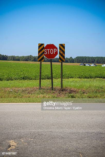 Stop Sign On Peanut Field Against Clear Sky