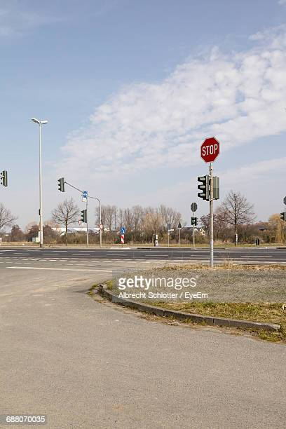 stop sign on road against sky - albrecht schlotter stock photos and pictures