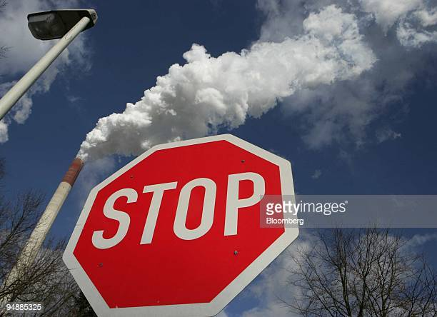 Stop sign stands in front of a smokestack at the E.ON-owned Scholven coal-powered electricity plant near Gelsenkirchen, Germany, on Wednesday, March...