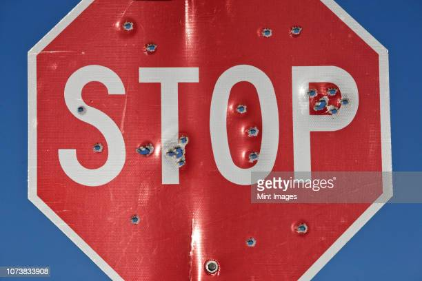 a stop sign that has been shot multiple times with a high powered rifle. - bullet hole stock pictures, royalty-free photos & images