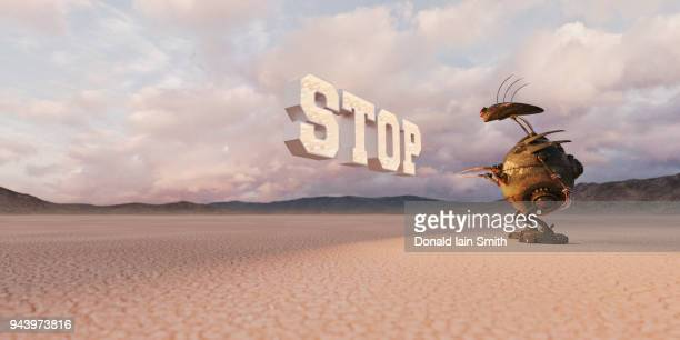 Stop: sign with light bulbs floating in desert with robot patiently waiting