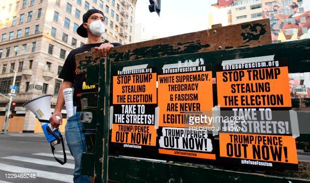 """Stop Stealing the Election"" placards are displayed on the side of a truck as activists gather for a rally in downtown Los Angeles, California on..."