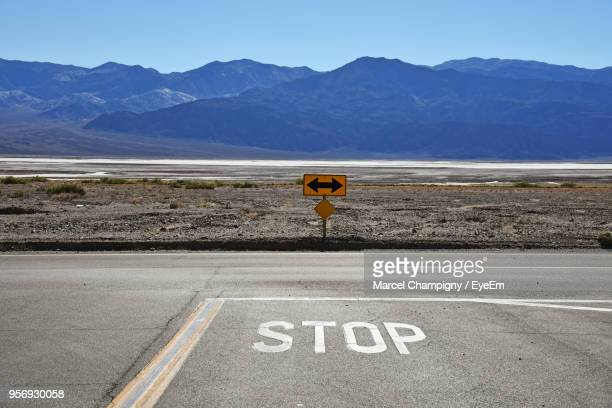 stop text on road by mountains against clear sky - chevron road sign stock pictures, royalty-free photos & images