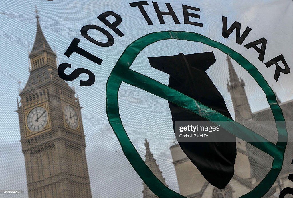 Stop the War Coalition supporters hold up a banner outside the Houses of Parliament on December 2, 2015 in London, England. A day long debate on whether Britain should become involved with airstrikes targetting Islamic State targets in Syria will end in a vote at 10pm tonight.