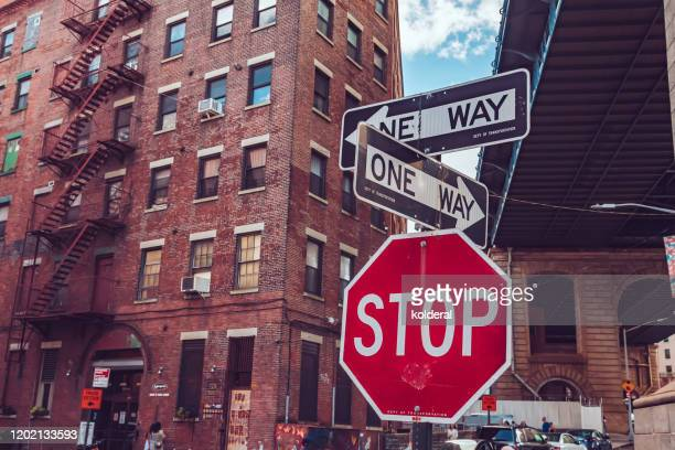 stop traffic sign and one way directions under brooklyn bridge in new york - one direction stock pictures, royalty-free photos & images