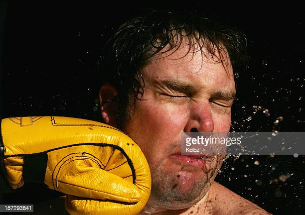 A stop-action photo of a boxing glove striking a man's face