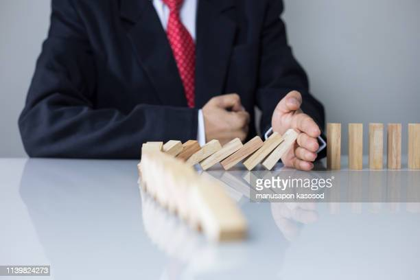 stopping the domino effect concept for business solution, strategy and successful intervention - risk stock pictures, royalty-free photos & images