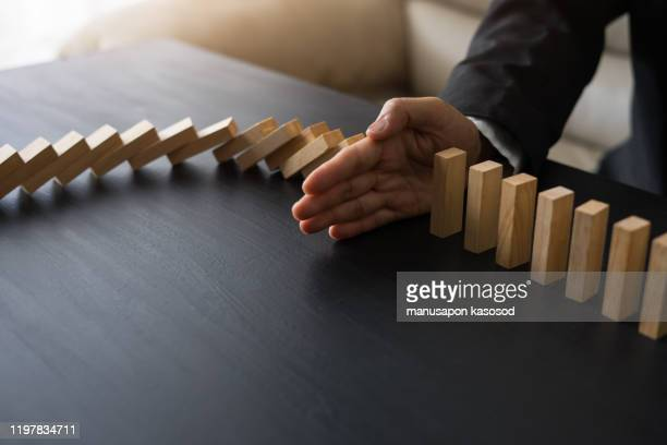 stopping the domino effect concept for business solution, strategy and successful intervention - kontinuität stock-fotos und bilder