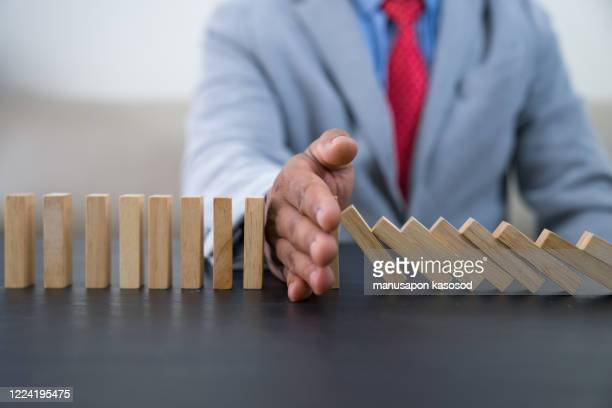 stopping the domino effect concept for business solution, strategy and successful intervention - strategy stock pictures, royalty-free photos & images