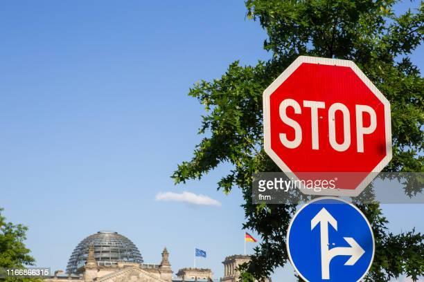 stop-signwith reichstag building in the background (berlin, germany) - demokratie stock-fotos und bilder