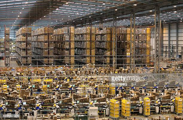 Storage racks stand beyond employees as they process customer orders at one of Amazoncom Inc's fulfillment centers in Peterborough UK on Tuesday Nov...