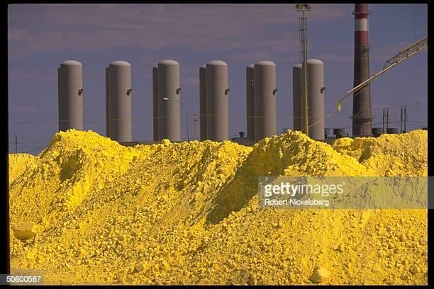 Storage tank-like structures framing sulphurous yellow pile , at Tengiz oil fields Tengiz Chevroil oil & gas refinery, Kazakh/Chevron joint venture.