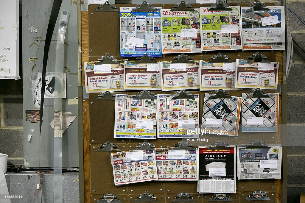 Store advertisements hang on a sample board next to a collator machine at the Washington Post newspaper production facility in Springfield, Virginia, U.S., on Friday, July 12, 2013. The Washington Post began publishing on Thursday, Dec. 6, 1877, and had a circulation of 10,000. The newspaper contained four pages and cost three cents a copy. Photographer: Andrew Harrer/Bloomberg via Getty Images