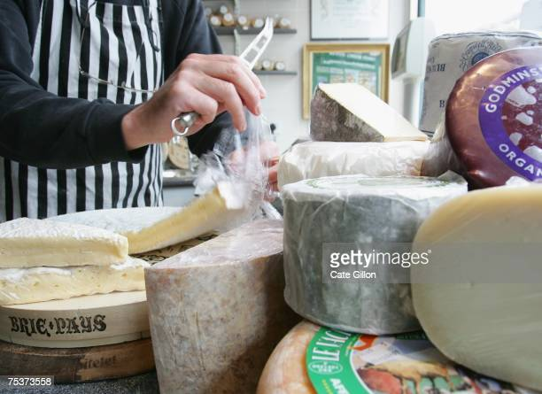 A store assistant cuts brie which can contain between 45 and 60 percent fat for a customer in a cheese store on July 12 2007 in London England...