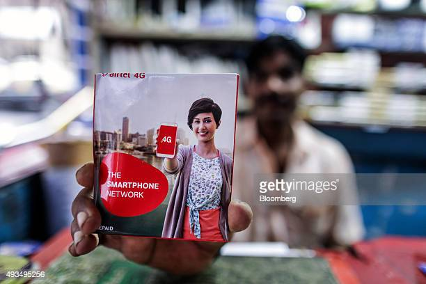 A store assistant holds a Bharti Airtel Ltd sim card pack for an arranged photograph in Mumbai India on Monday Oct 19 2015 Bharti Indias largest...