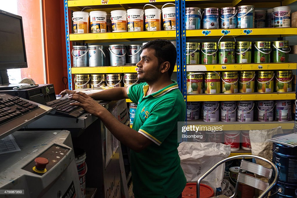 A store assistant operates a paint mixing machine at the HLS Hardware & Trading store the Parklands area of Klang, Selangor, Malaysia, on Wednesday, May 27, 2015. Malaysia's ringgit fell for a sixth day on June 1, in the longest stretch of losses since 2013 as falling oil prices weigh on the nation's finances. Photographer: Sanjit Das/Bloomberg via Getty Images