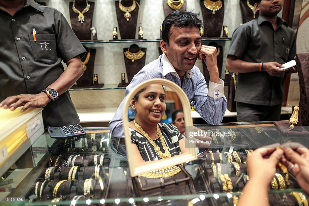 A store assistant serves a customer reflected in a mirror as she tries on gold jewelry in the Dwarkadas Chandumal Jewelers store in the Zaveri Bazaar area of Mumbai, India, on Thursday, Feb. 26, 2015. India's Finance Minister Arun Jaitley will present this year's budget on February 28. Speculation that Prime Minister Narendra Modi's policies will boost economic growth has propelled India's Sensex to the world's third-biggest gain among major markets during the past 12 months. Photographer: Dhiraj Singh/Bloomberg via Getty Images