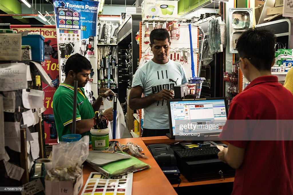 Store assistants serve a customer at the check-out of the HLS Hardware & Trading store in the Parklands area of Klang, Selangor, Malaysia, on Wednesday, May 27, 2015. Malaysia's ringgit fell for a sixth day on June 1, in the longest stretch of losses since 2013 as falling oil prices weigh on the nation's finances. Photographer: Sanjit Das/Bloomberg via Getty Images