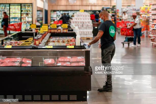 Store associate cleans the meat case at the Local Market Foods store in Chicago, Illinois, on April 8 during the coronavirus outbreak.