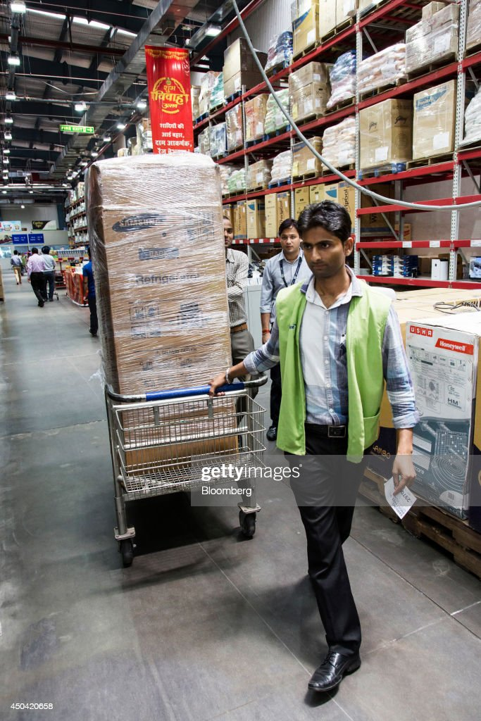 A store attendant moves a Samsung Electronics Co refrigerator in a shopping cart at a Walmart India Pvt Best Price Modern Wholesale store in the town.