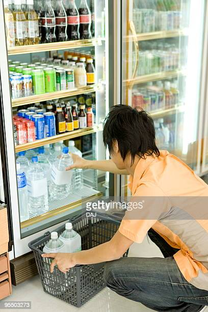 store clerk arranging products - convenience store stock photos and pictures