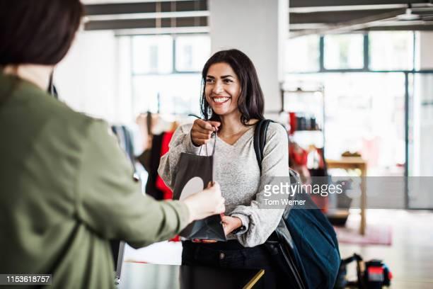 store clerk handing customer purchased items - kaufen stock-fotos und bilder