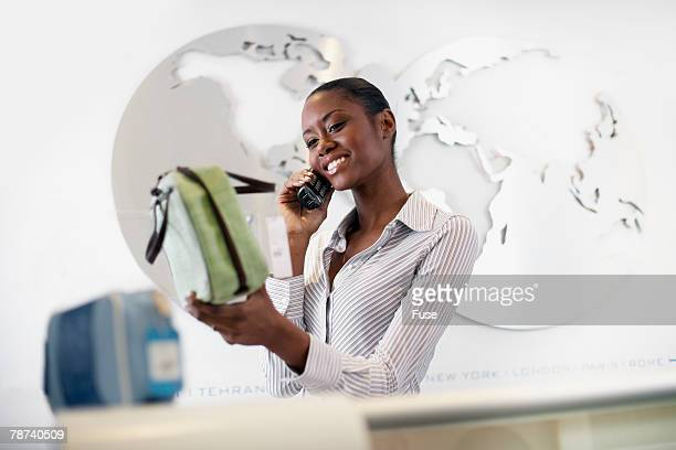 store clerk holding purse and talking on phone - black purse stock pictures, royalty-free photos & images
