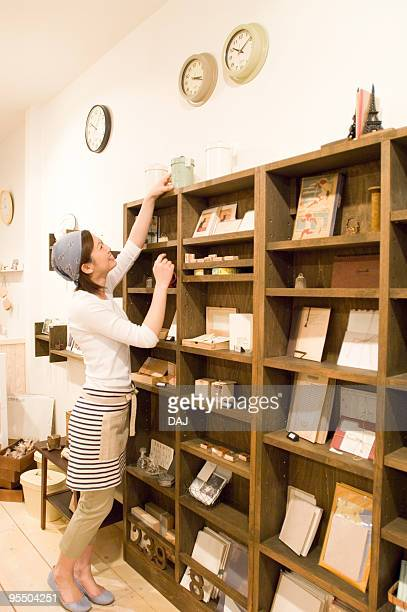 Store clerk trying to reach product on bookshelf