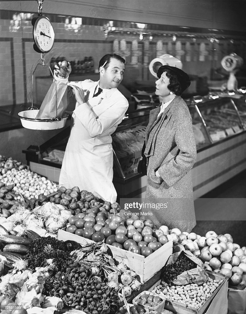 Store clerk weighing tomatoes for client (B&W) : Stock Photo