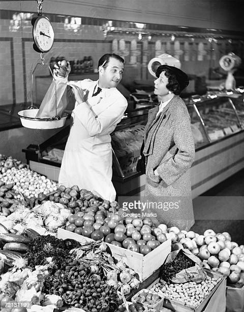 store clerk weighing tomatoes for client (b&w) - black and white vegetables stock photos and pictures
