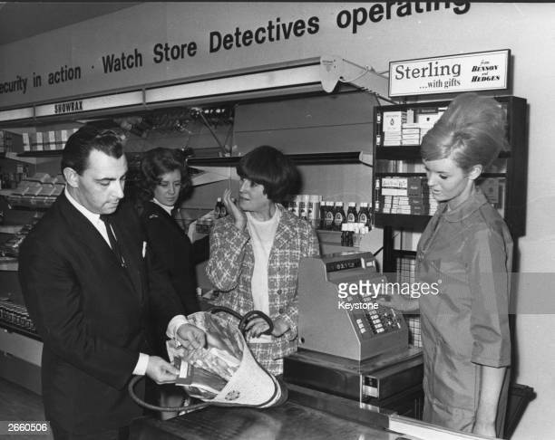 A store detective showing how a shoplifter can use a false lining to hide stockings during a demonstration at 'Shopshow International' Earl's Court...