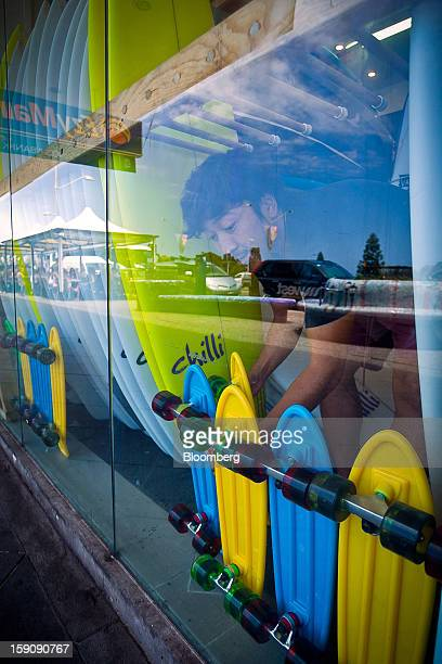 A store employee arranges skateboards next to surfboards in the window display of a surf shop at Bondi Beach in Sydney Australia on Monday Jan 7 2013...