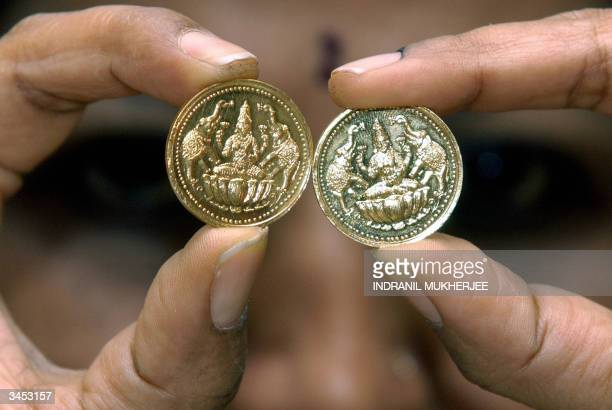 Store employee at Ganjam jewellers displays specially designed gold coins with an embossed image of Hindu Goddess Lakshmi with a retail value of Rs....