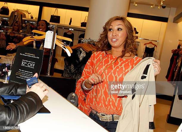 A store employee checks out a guest as Adrianna Costa hosts bebe at Miracle Mile's 'Bold New Look' event on January 12 2012 in Las Vegas Nevada