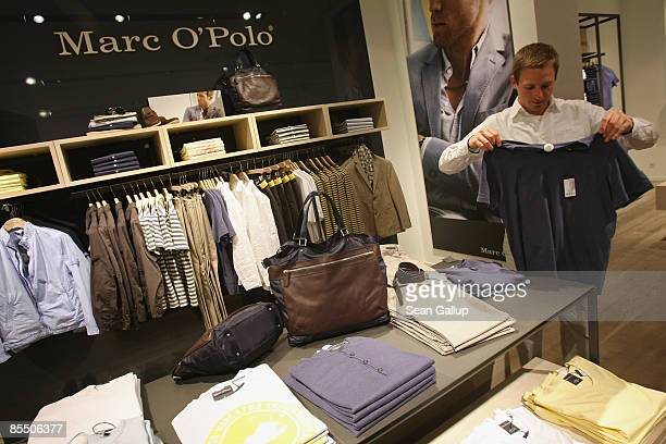A store employee folds a shirt at a new store of Swedishbased fashion retailer Marc O'Polo at the store's opening on March 19 2009 in Berlin Germany...