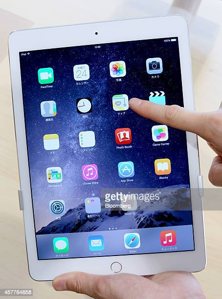 A store employee points at a 'Maps' icon on an Apple Inc new iPad Air 2 tablet displayed at a SoftBank Corp store in the Ginza district of Tokyo...