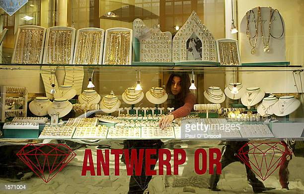 A store employee rearranges a window display in a jewelry shop October 31 2002 in Antwerp Belgium The gem traders in Antwerp are under pressure to...