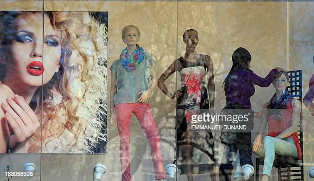 A store employee sets up a window display at a cloth shop in New York March 4 2013 AFP PHOTO/EMMANUEL DUNAND