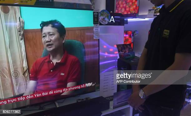 A store employee watches a screen showing Trinh Xuan Thanh speaking in a clip aired by Vietnam's state television VTV in Hanoi on August 4 2017...