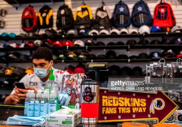 A store employee wearing a facemask looks at his phone near Washington Redskins merchandise for sale at a sports store in Fairfax Virginia on July 13...