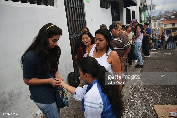A store employee writes numbers on people's wrists as they queue at dawn to buy basic foodstuffs on March 9 2014 in San Cristobal the capital of...