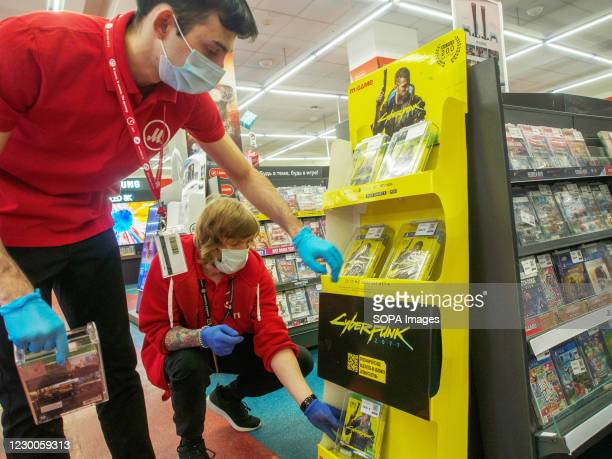 Store employees wearing face masks and gloves display game discs on the shelves. Cyberpunk 2077 is a 2020 action role-playing video game on sale...