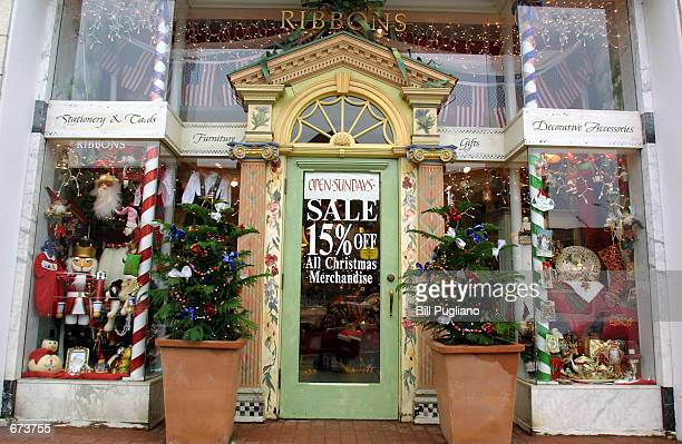 A store front is decorated for the Christmas shopping season with both trees and sale signs November 27 2001 in Birmingham Michigan